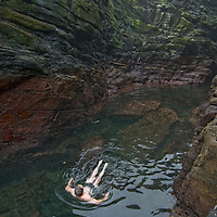 Geo tourists swim in a frigid, eerie gorge below the Devil's Nose at West Point Island in Britain's  Falkland Islands.
