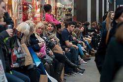 © Licensed to London News Pictures./14/2013. London, UK. Christmas shoppers have a rest on Oxford Street during the Christmas shopping season.Photo credit : Peter Kollanyi/LNP