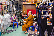 06 JUNE 2013 - BANGKOK, THAILAND:     A woman talks to Buddhist monks who stopped in her wholesale clothing shop on their morning alms rounds in Bobae Market in Bangkok. Bobae Market is a 30 year old market famous for fashion wholesale and is now very popular with exporters from around the world. Bobae Tower is next to the market and  advertises itself as having 1,300 stalls under one roof and claims to be the largest garment wholesale center in Thailand.       PHOTO BY JACK KURTZ