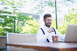 Businessman working on laptop in outdoor cafe and smiling, Munich, Bavaria, Germany