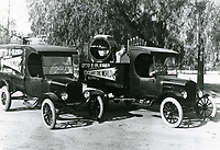 1930 Otto K. Olesen lighting truck. Man is playing a portable organ in the truck