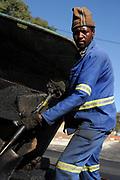 Wegwerker schept teerasfalt voor aanleg nieuwe wegen, Port Elizabeth WK Zuid Afrika.