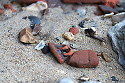 Brick and pottery fragments on the Thames foreshore, London, UK.