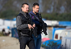 © Licensed to London News Pictures. 25/10/2016. Calais, France.  French police with tear gas gun, watch over the migrant and refugee camp in Calais, known as the 'Jungle'. French authorities have moved thousands of refugees and migrants living at the makeshift living area on the French coast, with some still refusing to leave. . Photo credit: Ben Cawthra/LNP
