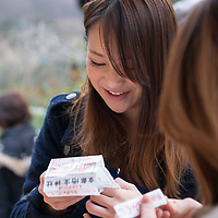 """Voyagers traveled on the """"Kyoto Culture and Sweets"""" field program to the Kinkakuji Temple, Nijo Castle, and Kiyomizu (Pure Water) Temple before learning how to make traditional Japanese sweets. A Japanese girl reads her fortune on a slip of paper at Jishu-jinga, a separate shrine located above Kiyomizu-dera's main hall."""