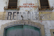 Fading garage lettering including French car manufacturer Renault, on 21st May 2017, in Fabrezan, Languedoc-Rousillon, south of France.