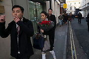 Chinese woman with a bunch of red roses on Valentines Day in London, England, United Kingdom.