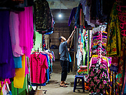 04 AUGUST 2017 - PAYANGAN, BALI, INDONESIA: A man sets up his clothing shop in the local market in Payangan, about 45 minutes from Ubud. Bali's local markets are open on an every three day rotating schedule because venders travel from town to town. Before modern refrigeration and convenience stores became common place on Bali, markets were thriving community gatherings. Fewer people shop at markets now as more and more consumers go to convenience stores and more families have refrigerators.      PHOTO BY JACK KURTZ