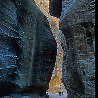 Travelers hike through the Siq, a massive slot canyon leading the the ancient city of Petra, a World Heritage Site in Jordan.