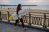 A girl with the surfboard under her arm goes to surf. Donostia (Basque Country). May 7, 2020. Some outdoor activities have been allowed as Spain is going through the plan of downscaling following an ongoing plan to leave the confinement ordered by the Spanish government to prevent the spread of the COVID-19. (Gari Garaialde / Bostok Photo)