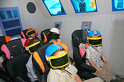 Children wearing VR helmets in a space shuttle simulator