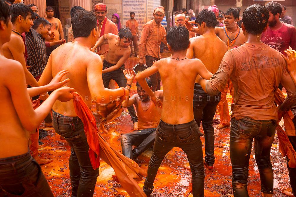 A group of boys hit a man with wet clothes at the Huranga festival, Dauji temple, Baldeo, India. Photo © robertvansluis.com