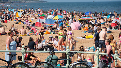 Edinburgh, Scotland, UK. 31 July, 2020. Temperature of 25C and sunshine brought huge crowds to Portobello Beach outside Edinburgh. Several large groups of teenagers were enjoying beach and alcoholic drinks were very popular.