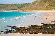 Coastal scenery with busy crowded sandy beach, Sennan Cove, Land's End,  Cornwall, England, UK