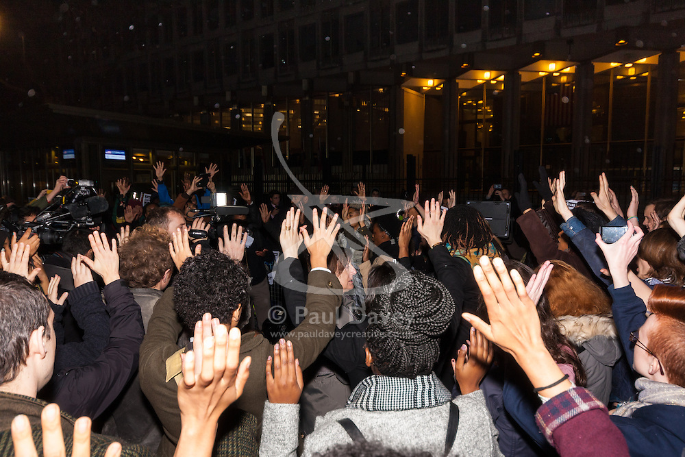 """London, November 26th 2014. A vigil for teenager Mike Brown who was shot dead by a policeman in Ferguson, Missouri this year, takes place outside the US embassy in London. Anti-racism and human rights campaigners called the 'emergency' protest following a court verdict that clears Police Officer Darren Wilson of murder. PICTURED: The crowd makes a """"Hands-up! Don't shoot!"""" gesture in protest against police shootings."""