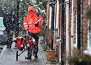 © Licensed to London News Pictures. 14/01/2013. Amersham, UK A postman delivers post in the snow. People and snow in Amersham in south-east Buckinghamshire. Snow hits the many parts of the UK today 14th January 2013. Photo credit : Stephen Simpson/LNP