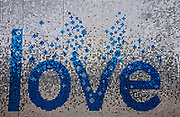 Glittering sign displaying the word 'love'. Blue and silver discs for the word on this hanging display.