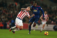 Paul Pogba of Manchester Utd holds off a strong challenge from Glenn Whelan of Stoke city.  Premier league match, Stoke City v Manchester Utd at the Bet365 Stadium in Stoke on Trent, Staffs on Saturday 21st January 2017.<br /> pic by Andrew Orchard, Andrew Orchard sports photography.