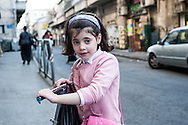 A young girl pauses with her scooter in the Mea Sharim neighborhood of Jerusalem