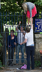 © licensed to London News Pictures. 01/05/2011. Oxford, UK. Oxford Brookes student scale a fence Angel And Grayhound Meadow in Oxford after swimming in the River Cherwell underneath the Magdalen Bridge bridge in Oxford, Oxfordshire today (01/05/02011) as part of  May Day celebrations. Revelers where prevented from jumping from the bridge which is tradition. Please see special instructions for usage rates. Photo credit should read Ben Cawthra/LNP