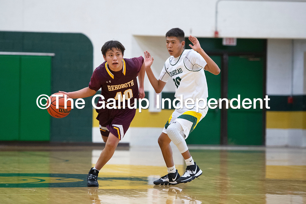 Rehoboth's Casey Joe (40) dribbles the ball down the court as Thoreau's Rolando Chacho (30) defends Tuesday night in Thoreau.