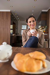 Mid adult woman drinking cup of coffee at breakfast table, Munich, Bavaria, Germany