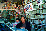 Woman and child in video shop, Paro, Bhutan