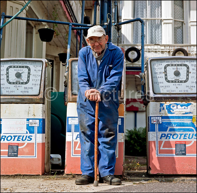 John Stoke standing in front of his garage, N.J. Stoke Garage, with old fashioned swing petrol pumps on the 19th July 2008 in Stockbridge in the United Kingdom.