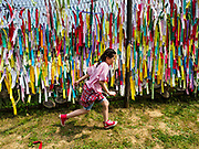 09 JUNE 2018 - IMJINGAK, PAJU, SOUTH KOREA: South Korean school children run past prayer flags hanging on a fence near the northernmost point on the South Korean side of the Korean DMZ in Imjingak. Imjingak is a park and greenspace in South Korea that is farthest north most people can go without military authorization. The park is on the south bank of Imjin River, which separates South Korea from North Korea and is close the industrial park in Kaesong, North Korea that South and North Korea have jointly operated.     PHOTO BY JACK KURTZ