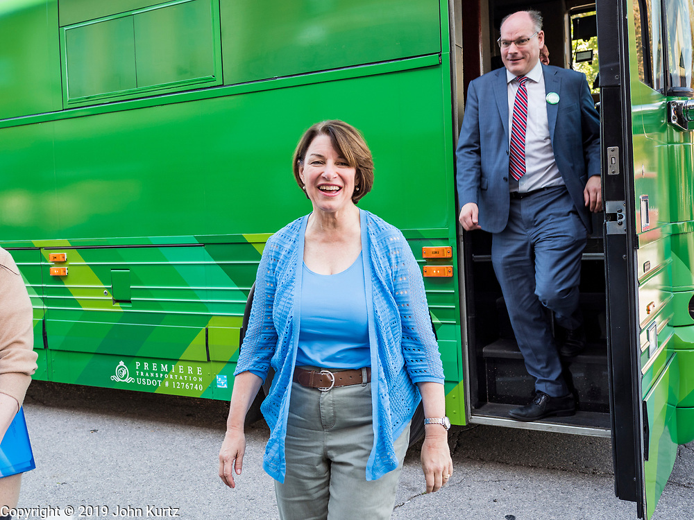 18 OCTOBER 2019 - SIGOURNEY, IOWA: US Senator AMY KLOBUCHAR (D-MN) and her husband, JOHN BESSLER, get off the bus she is campaigning in at a stop in Sigourney, IA. Sen. Klobuchar is on barnstorming bus tour of southeast Iowa this weekend. She is campaigning to be the Democratic nominee for the US Presidency. In addition to campaign meet and greet events, she stopped at a biofuels plant to learn about the difficulties farmers and biofuels producers face because of the trade war with China. Iowa holds the first selection event of the Presidential election cycle. The Iowa caucuses are Feb. 3, 2020.         PHOTO BY JACK KURTZ