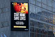 Large scale HM Government, and NHS advertising board advice to stay at home and help save lives during the third national coronavirus lockdown in Birmingham city centre, which is deserted apart from a few people on 7th January 2021 in Birmingham, United Kingdom. Following the recent surge in cases including the new variant of Covid-19, this nationwide lockdown, which is an effective Tier Five, came into operation yesterday, with all citizens to follow the message to stay at home, protect the NHS and save lives.