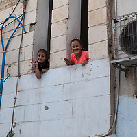 Children in the Aida Camp in Bethlehem look from windows. The West Bank has 19 refugee camps and 741,409 registered refugees. These are people who lost both home and means of livelihood when Israel occupied Palestinian territories by force in 1948.