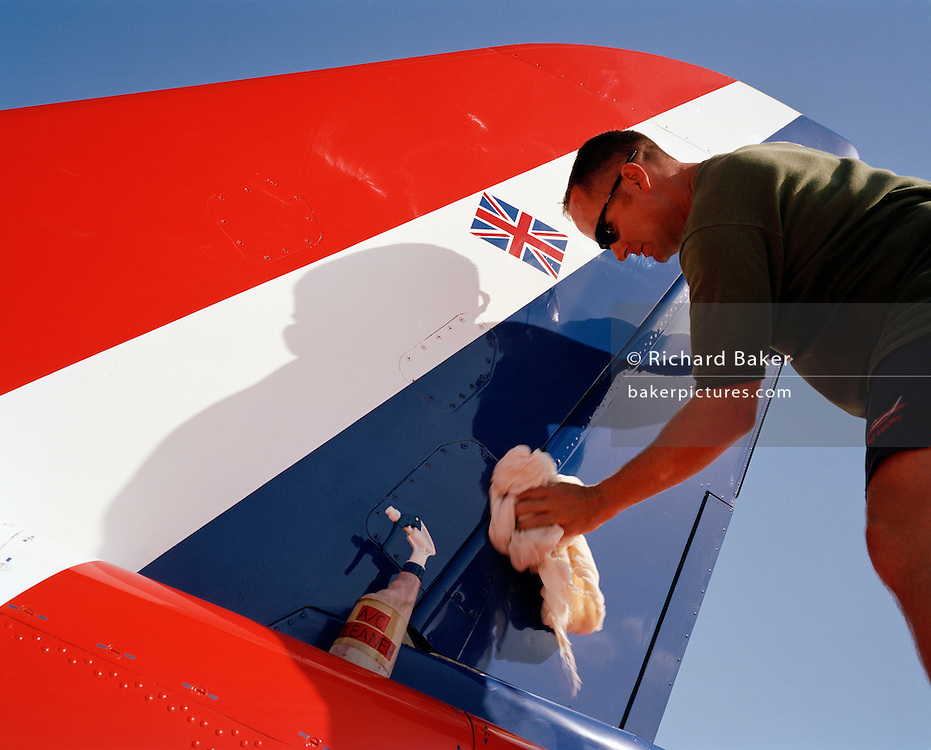 Ground crew of the elite 'Red Arrows', Britain's prestigious Royal Air Force aerobatic team polish the aircraft's flying surfaces using wool and cleaning fluid on the morning of the team's PDA Day. PDA (or 'Public Display Authority'), is a special test flight when their every move and mistake is assessed and graded. Corporal Faulder is to buff up the airplane for an extra special shine on such an important day and we see the UK's Union Jack flag on the side of the diagonal stripes of the tail fin. The Red Arrows ground crew take enormous pride in their role as supporting the aviators whose air displays are known around the world. Blues like Mal outnumber the pilots 8:1. Without them, the Red Arrows couldn't fly.