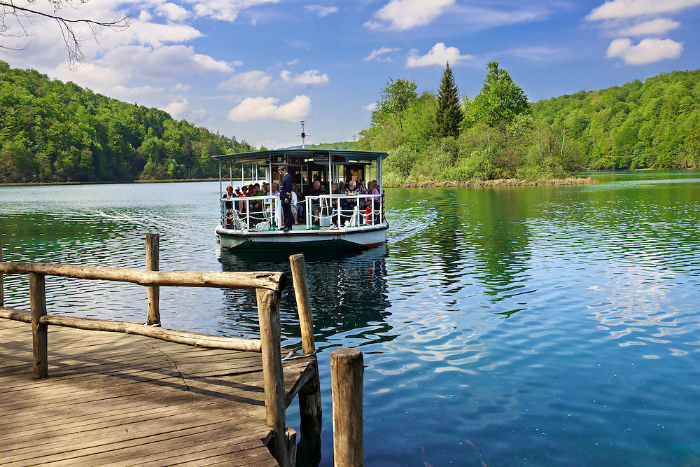 Electric boat ferrying tourists across one of Plitvice lakes. Plitvice ( Plitvika ) Lakes National Park, Croatia. A UNESCO World Heritage Site .<br /> <br /> Visit our CROATIA HISTORIC SITES PHOTO COLLECTIONS for more photos to download or buy as wall art prints https://funkystock.photoshelter.com/gallery-collection/Pictures-Images-of-Croatia-Photos-of-Croatian-Historic-Landmark-Sites/C0000cY_V8uDo_ls