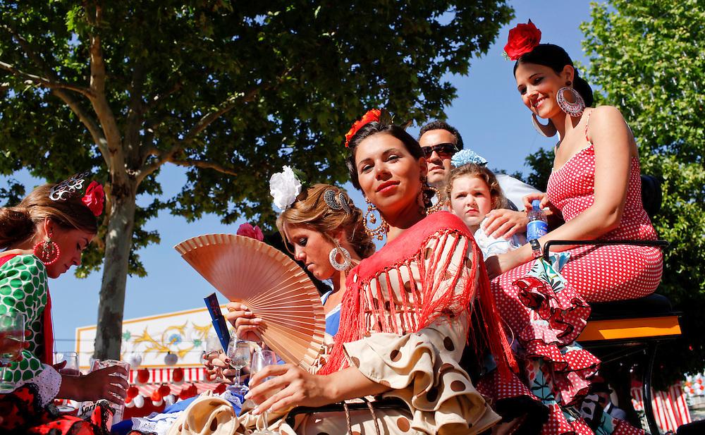 """Abril, 20, 2010. Lifestyle/Spain. Seville April Fair. A crowd of people attend today the first real day of the """"feria de Abril"""" of Seville. Many women dresses with the traditional costume of """"Flamenca"""" and the people walk,  dance """"sevillanas"""" (typical sevilian dance) and drink """"rebujito"""" (typical drink of the """"Feria de Abril"""" made by the youngdry wine """"Manzanilla""""  and carbonated drink...Una multitud de personas asisten hoy al primer día real de la feria de Abril de Sevilla. Muchas mujeres se visten con el traje tradicional de """"flamenca"""" y pasean por el recinto ferial mientras bailan, beben """"rebujito"""" (bebida típica de la feri de Abril hecha de """"Manzanilla"""" y bebida gaseosa y montan a caballo o en carruaje."""