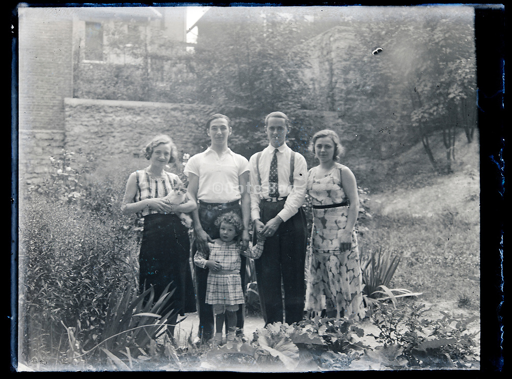 family with friends  standing in backyard garden France circa 1930s