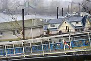 Nederland, Gennep, 31-12-2016De woonboten in Heijen bij Gennep komen steeds schever te liggen omdat het water in de Maas nog niet op het laagste punt is gekomen. Gisteren botste een tanker, binnenvaartschip, op de stuw van Grave en maakte deze kapot. Hierdoor liep het water  weg en kwam een meter of twee lager te liggen. Een van de eigenaren probeert zijn woonboot vlot te trekken met hulp van vrienden. Het lukt niet.Foto: Flip Franssen