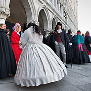 """VENICE, ITALY - FEBRUARY 19:  Members of the association """"Amici del Carnevale di Venezia"""" wearing 19th century costumes pose in St Mark Square on February 19, 2011 in Venice, Italy. The fountain pouring wine features today during the Gran brindisi a Venezia or Grand Toast in Venice, the opening ceremony of this year Carnival ."""