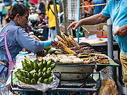 29 NOVEMBER 2015 - BANGKOK, THAILAND:  A food vendor sells grilled vegetables on her last day in the Amulet Market on Maharat Road in Bangkok.  Hundreds of vendors used to sell amulets and Buddhist religious paraphernalia to people in the Amulet Market, a popular tourist attraction along Maharat Road north of the Grand Palace near Wat Maharat in Bangkok. Bangkok municipal officials announced that they are closing the market and forcing vendors to relocate to an area about one hour outside of Bangkok. The closing of the amulet market is the latest in a series of municipal efforts to close and evict street vendors and markets from areas that have potential for redevelopment. The street vendors were evicted from the area on Sunday, Nov. 29.      PHOTO BY JACK KURTZ