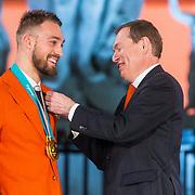 NLD/Den Haag/20180323 - Huldiging Olympische en Paralympische medaillewinnaars, Bruno Bruins, minister voor medische zorg en sport reikt de onderscheidingen uit aan Kjeld Nuis