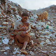 Sarah Nasimiyu is 45 years old and is pictured with her two-year-old Joshua. She has four other children ranging in age from three to thirteen years old. They all work on the dumpsite. She separated from her husband in 2008 because he was always drunk and couldn't be responsible. She brings Joshua with her to the dumpsite – where she sorts through rubbish in the morning and then sells snacks to the other workers in the afternoon, and has been doing so for four years.<br /> <br /> The Mothers who work on Eldoret's main dump nick named by the locals,  ironically, as 'California' raise their children in Extreme poverty. The consequences for these children and their parents are tough; with disease, injury, substance abuse and even the threat of violence an everyday reality.