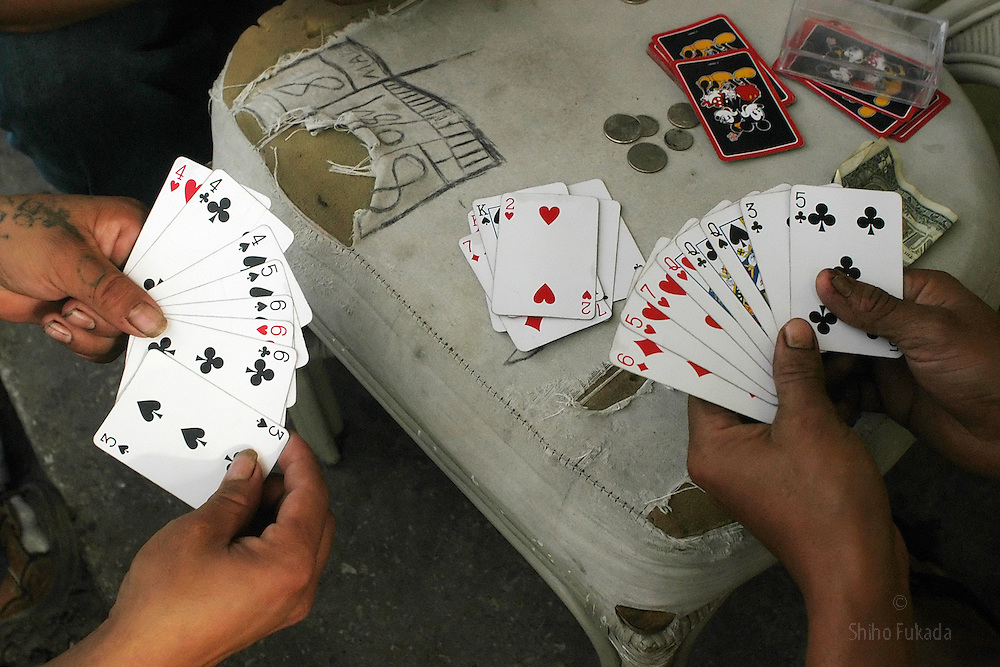 Migrant farm workers play cards after work in Immokalee, FL, Apr. 18, 2003.
