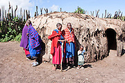 Maasai Women in traditional clothes outside of their hut Photographed in Kenya