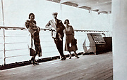 people on the walking deck of a large cruise passenger ship 1930s