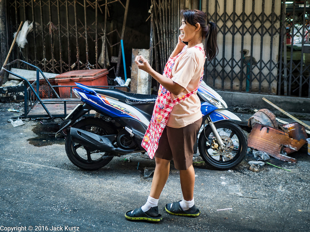 04 JANUARY 2016 - BANGKOK, THAILAND:       A street food vendor in Bang Chak Market talks on her cell phone before the market closed. The market closed January 4, 2016. The Bang Chak Market serves the community around Sois 91-97 on Sukhumvit Road in the Bangkok suburbs. About half of the market has been torn down. Bangkok city authorities put up notices in late November that the market would be closed by January 1, 2016 and redevelopment would start shortly after that. Market vendors said condominiums are being built on the land.   PHOTO BY JACK KURTZ