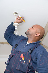 Electrician testing an electric light using special equipment,