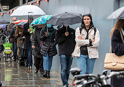 © Licensed to London News Pictures. 23/12/2020. London, UK. Last minute Christmas shoppers queue in the pouring rain outside Waitrose in Chelsea, South West London as fears grow that the whole of the UK will be plunged into Tier 4 restrictions after a Covid-19 mutation spread rapidly throughout the South East of England. Ministers have said that Downing Street is considering whether to add more areas of England to tougher Covid-19 restrictions after the new mutated strain continues to spread. Photo credit: Alex Lentati/LNP