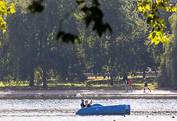 Licensed to London News Pictures. 16/09/2021. London, UK. Members of public Walkers enjoy the late summer sun on the serpentine in Hyde Park, London as weather forcasters predict a warmer few days ahead with highs of 24c for London and the South East. Photo credit: Alex Lentati/LNP
