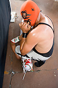 July 13, 2008 -- PHOENIX, AZ: Luchador Dr. Parker, bites the hand of his opponent Aguilita Guerrero (Little Eagle of Guerrero) during a Lucha Libre show at El Gran Mercado in Phoenix. Parker was the rudo (villian) in the show, Aguilita the tecnico (good guy). Lucha Libre is Mexican style wrestling. There are heros (Tecnicos) and villians (Rudos). The masks are popular as children's gifts and tourist mementos. As the size of the Mexican community in the Phoenix area has grown, attendance at the Lucha Libre shows has increased. Lucha Libre differs from American style entertainment wrestling in several ways, but principally the wrestlers are more acrobatic and rely less on body slams than American wrestling. The shows, which used to be held only periodically, are now held every week at El Gran Mercado, a flea market and swap meet that caters mostly to the Mexican community in Phoenix.   Photo by Jack Kurtz / ZUMA Press