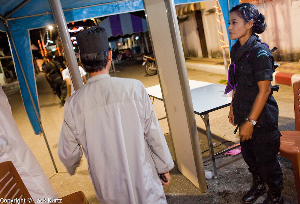 29 SEPTEMBER 2009 -- YARANG, PATTANI, THAILAND: Thai women Rangers, a paramilitary unit commanded by Thai Army officers, at a security checkpoint at a street fair in Yarang, Pattani, Thailand. The 39 women in the 44th Army Ranger Regiment are the only Thai women seeing front line active duty against Moslem insurgents in Thailand's deep south provinces of Pattani, Narathiwat and Yala. All of the other women serving in Thai security services are employed as office and clerical workers. The Ranger women are based at the Ranger camp in the Buddhist village of Baan Trokbon in Sai Buri district of Pattani province. The unit was formed in 2006 after Muslims complained about the way Thai soldiers, all men, treated Muslim women at roadblocks and during security sweeps. The women are frequently called upon to back up Thai regular army units when they are expected to encounter a large number of Muslim women. At least two of the women have been killed by Muslim insurgents. The unit has both Muslim and Buddhist members. Many of the women in the unit joined after either their fathers or husbands were killed by insurgents.   PHOTO BY JACK KURTZ